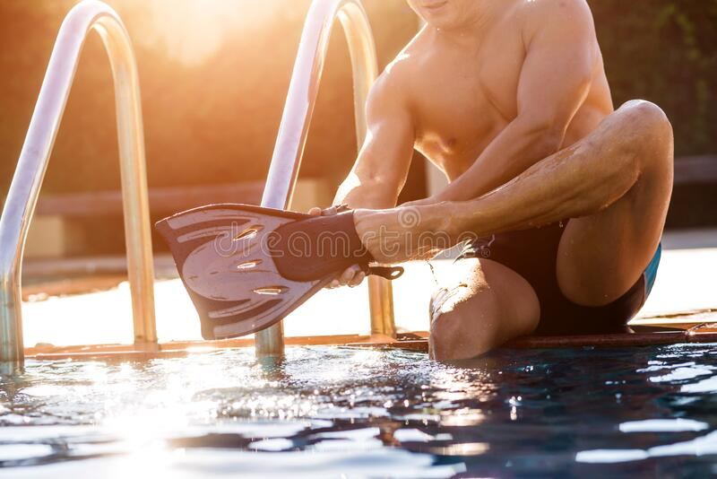 Young athletic man wearing flippers by the pool stock images