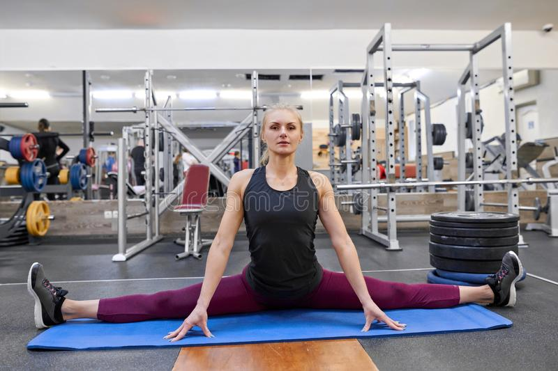 Young athletic muscular woman doing stretching workout in the gym, woman practicing yoga royalty free stock photography