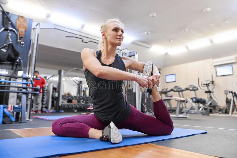 Young athletic muscular woman doing stretching workout in the gym, woman practicing yoga royalty free stock photo