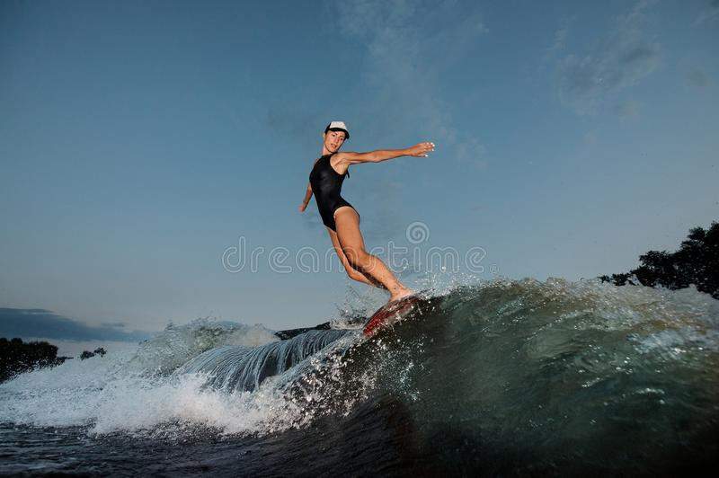 Young athletic nice woman riding on the orange wakesurf royalty free stock photography