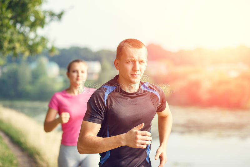 Young athletic people jogging outdoor near pond. Man and women doing run workout in the park stock photos
