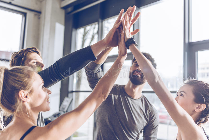 Young athletic people in sportswear giving high five in gym stock photography