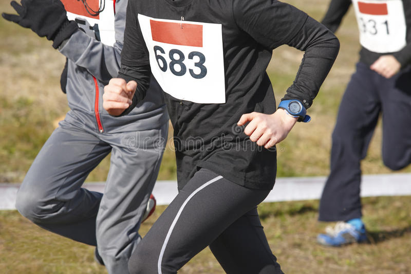 Young athletic runners on a cross country race. Outdoor circuit. Horizontal stock image