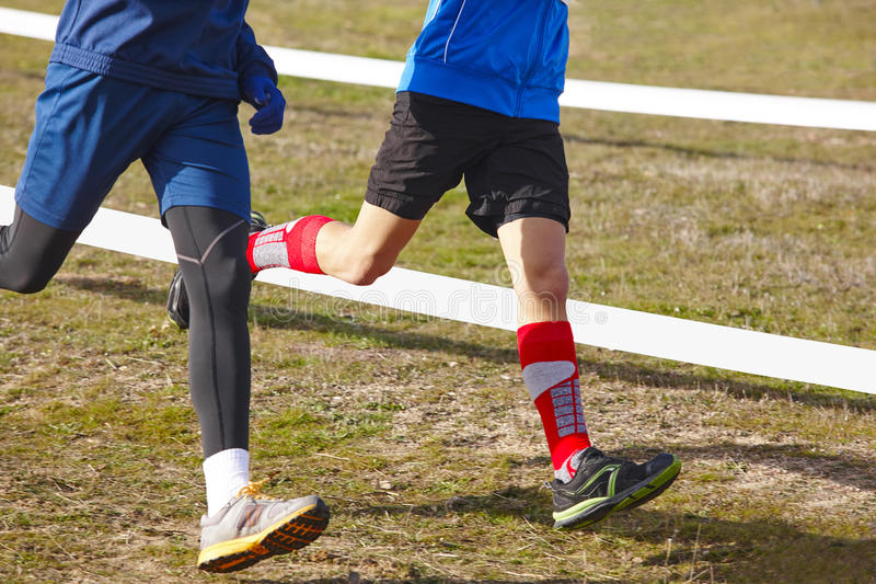 Young athletic runners on a race. Outdoor circuit. Horizontal stock image