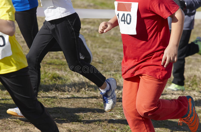 Young athletic runners on a race. Outdoor circuit. Horizontal stock photo