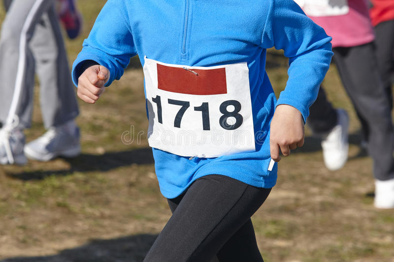 Young athletic runners on a race. Outdoor circuit. Horizontal royalty free stock photography