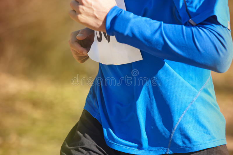 Young athletic runners on a race. Outdoor circuit. Horizontal stock photos