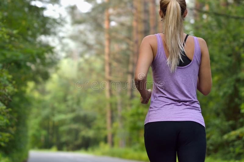 Young athletic sporty girl with long hair training in green forest during summer or autumn season. royalty free stock images