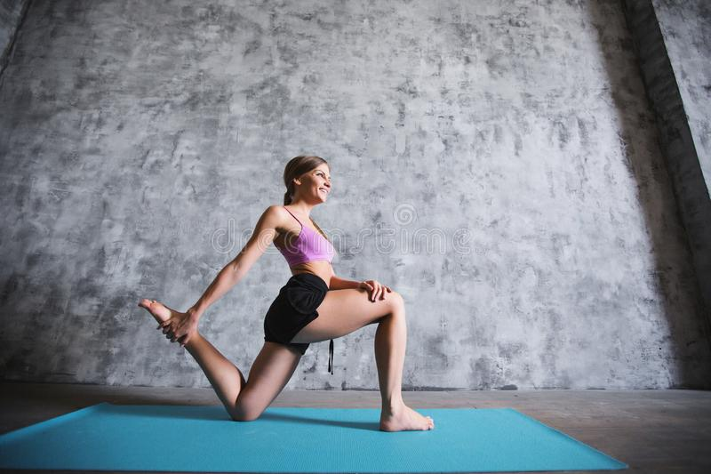 Young athletic sporty slim woman doing yoga exercise in the gym. royalty free stock photography