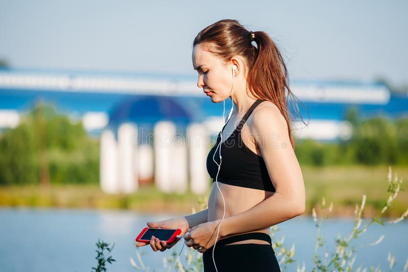 Young athletic woman on beach runner listening to music with headphones. Young athletic woman on the beach runner listening to music with headphones stock photos