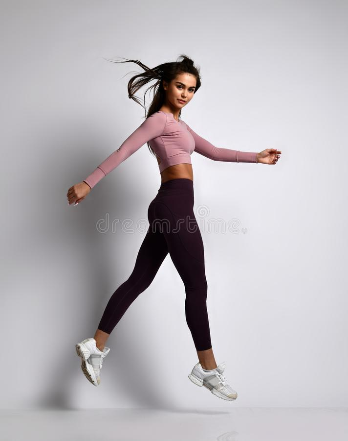 Young athletic woman brunette girl in a good shape in trendy sportswear walking in gym uniform does cardio exercises royalty free stock photos