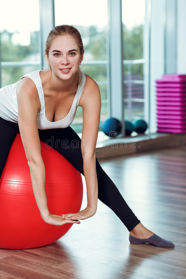 Young athletic woman doing exercises with fitness ball in gym royalty free stock images