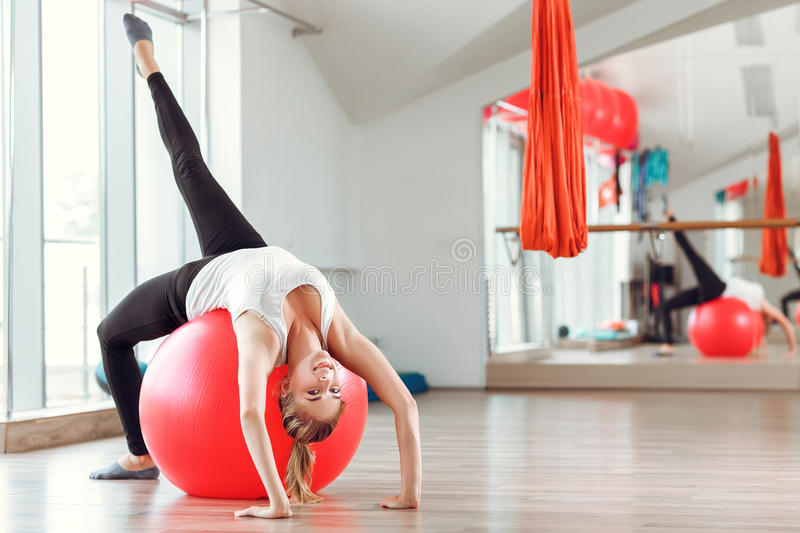 Young athletic woman doing exercises with fitness ball in gym royalty free stock image