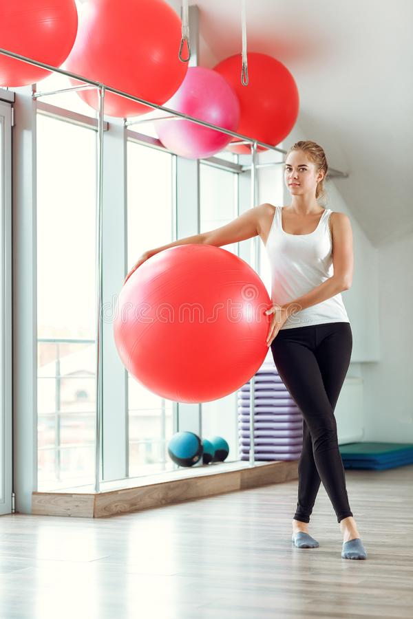Young athletic woman doing exercises with fitness ball in gym stock photo