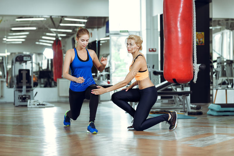 Young athletic woman doing exercises with personal fitness trainer royalty free stock photo