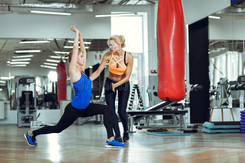 Young athletic woman doing exercises with personal fitness trainer stock images