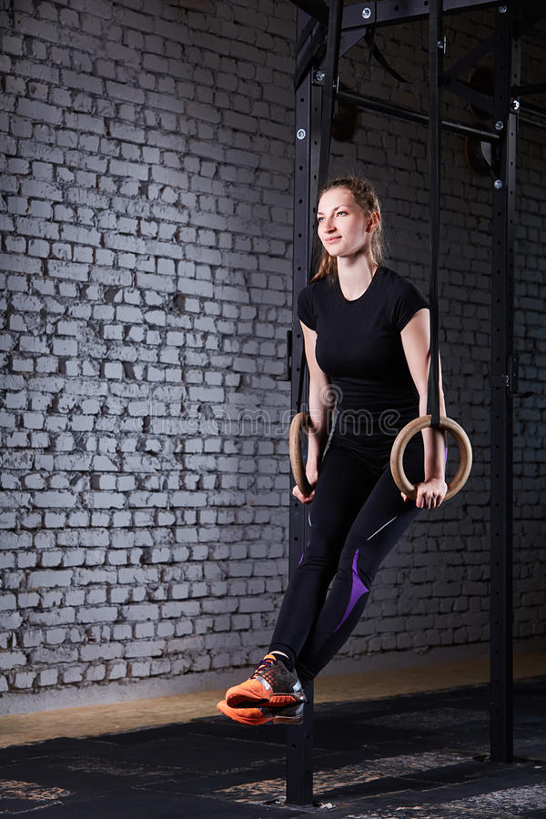 Young athletic woman doing pull-ups exercise with rings as cross fit workout against brick wall. royalty free stock image