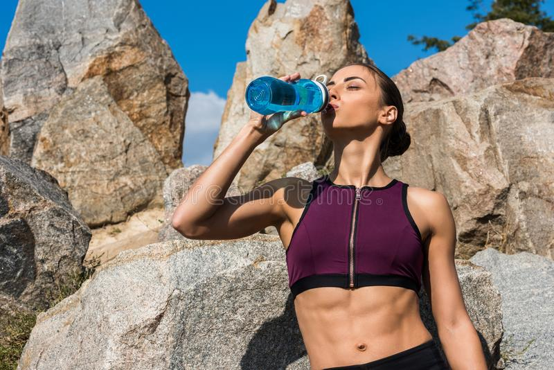 young athletic woman drinking water in front royalty free stock images