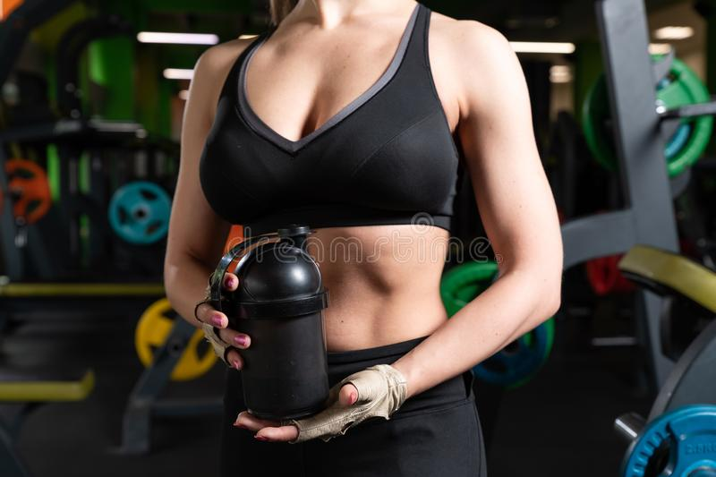 Young athletic woman drinking water in gym stock photos