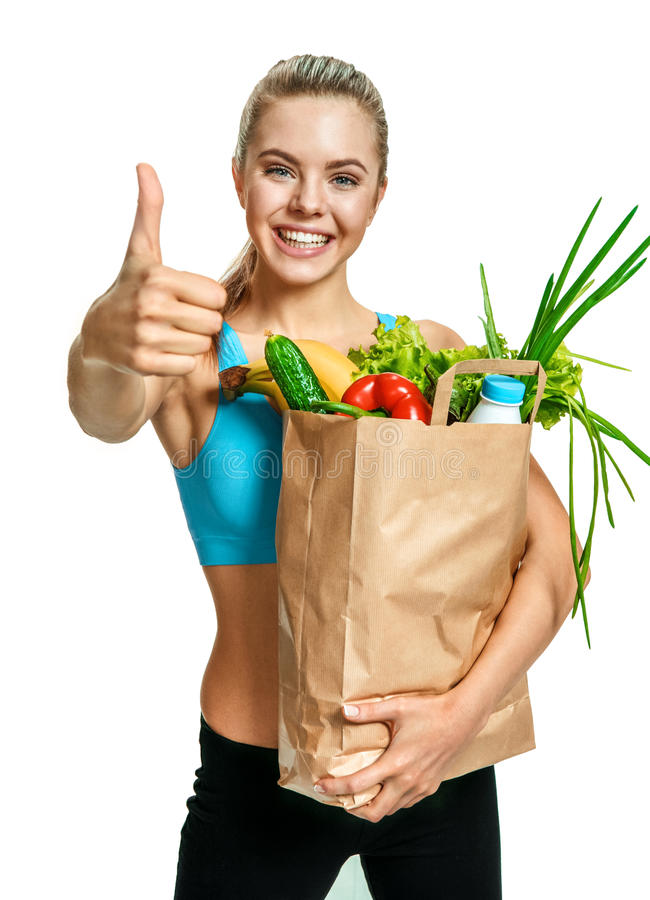 Young athletic woman gesturing thumb up with grocery bag full of healthy fruits and vegetables royalty free stock photos