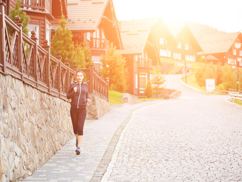 Young athletic woman jogging in mountain resort. Young athletic woman jogging on cobbled street in mountain village. Healthy summer hillside vacation background stock images