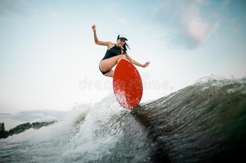 Young athletic woman jumping on the orange wakesurf stock images