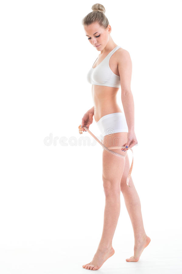young athletic woman measuring waist measuring tape, isolated over white background royalty free stock images