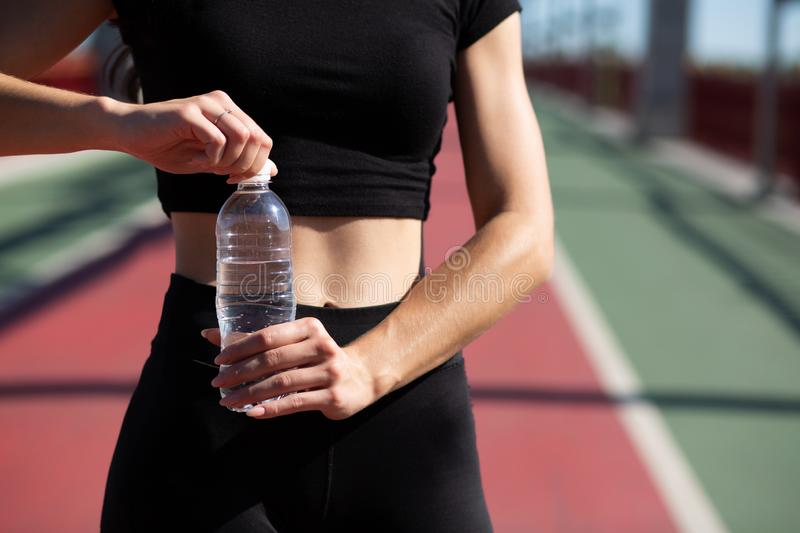 Young athletic woman opening water bottle during jogging at the royalty free stock photo