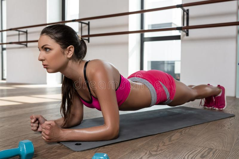 Young athletic woman performing an exercise plank on the floor in the gym stock images