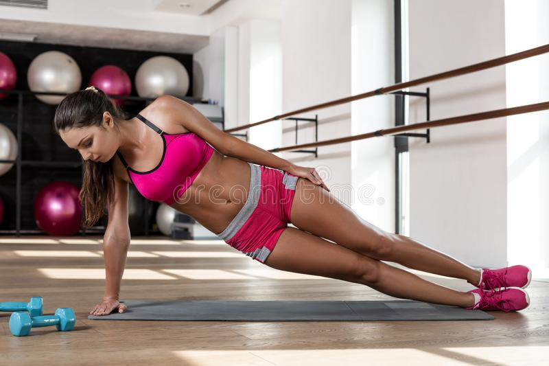 Young athletic woman performing an exercise plank on the floor in the gym stock image