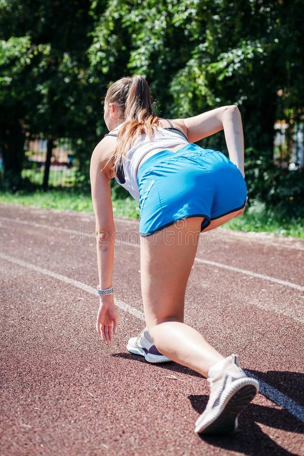 Young athletic woman preparing to run at stadium, outdoors. view from back. The concept of healthy lifestyle royalty free stock photography