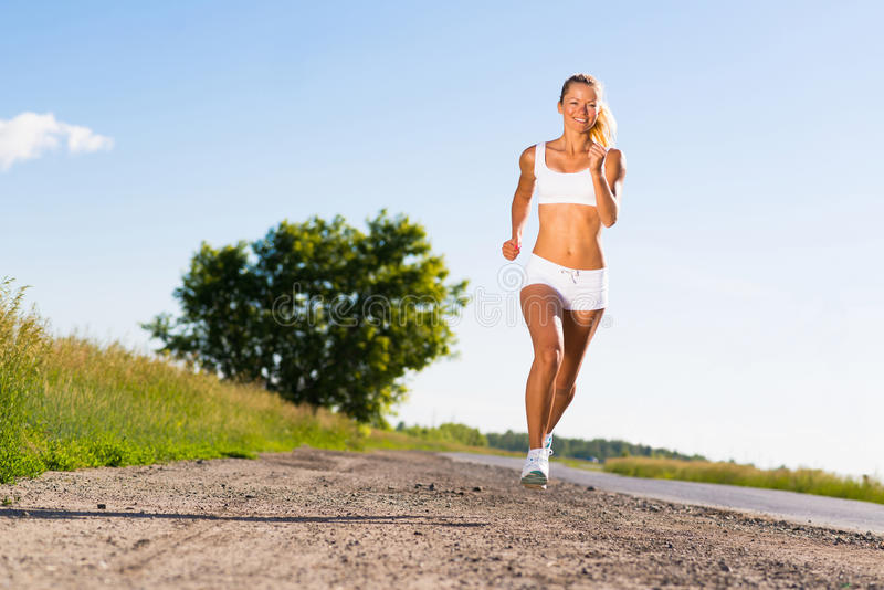 Young Athletic Woman Running On The Road Royalty Free Stock Images