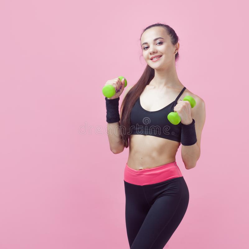 A young athletic woman, with a smile, in black sports top, doing aerobics on pink background with green light dumbbells. A young athletic woman, with a smile royalty free stock photos