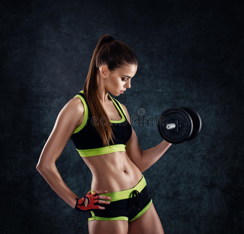 Young athletic woman in sportswear with dumbbells in studio against dark background. Ideal female sports figure. Fitness girl with royalty free stock photo