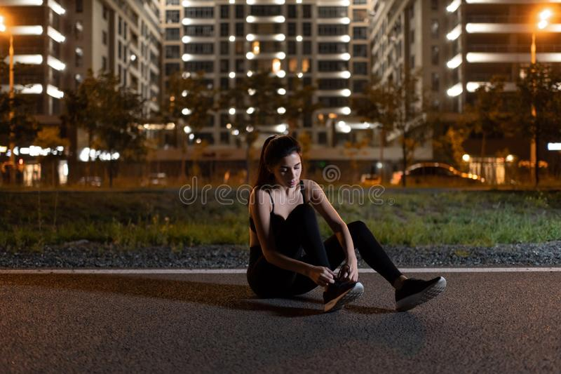 Sportswoman tying shoelaces during night workout. Young athletic woman in sportswear sitting on track and tying shoelaces while training on urban background at royalty free stock image