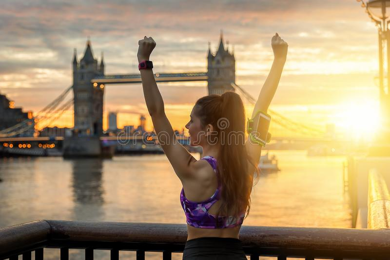 Female fitness model during morning workout in the urban city. Young, athletic woman in winner posing during sunrise in London; female fitness model during stock image