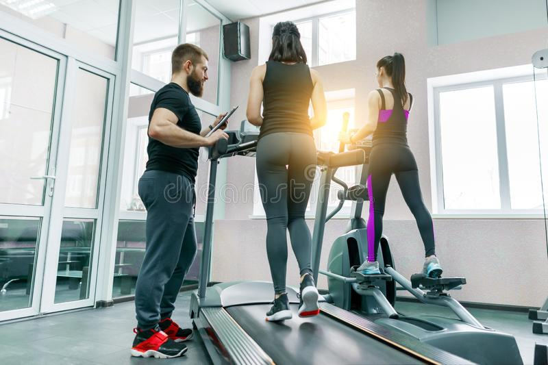 Young athletic women on treadmill, personal instructor coaching and helping client woman. Fitness, sport, training, people concept royalty free stock photography