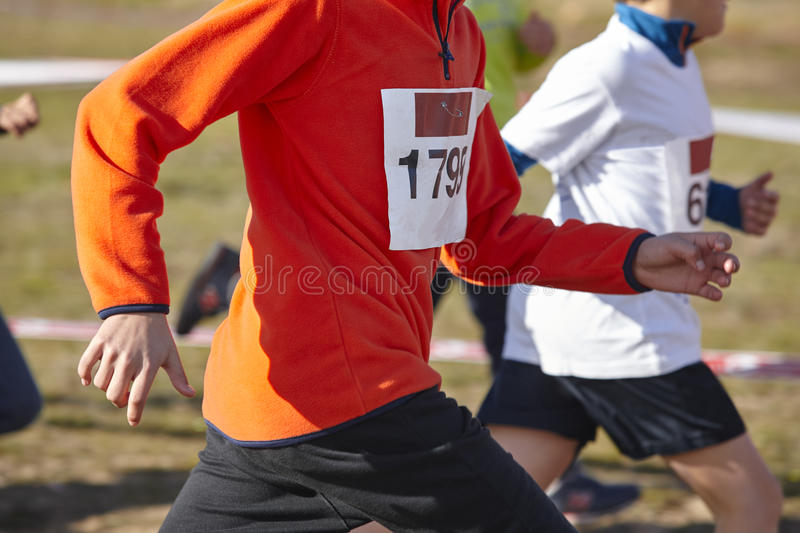Young athletics runners on a race. Outdoor circuit. Horizontal stock images