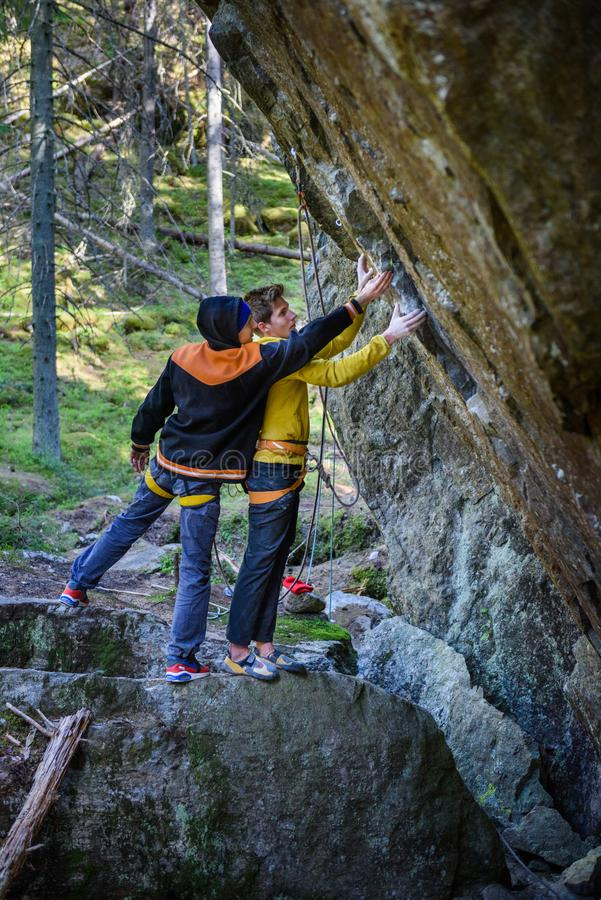 Young athlets exploring rock climbing routes in scandinavian forest royalty free stock photo