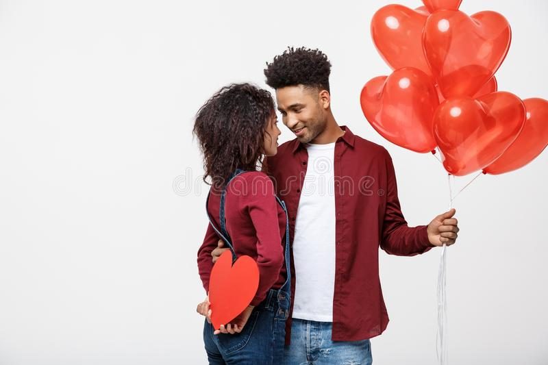 Young attactive African American couple holding heart balloon and paper. royalty free stock photos