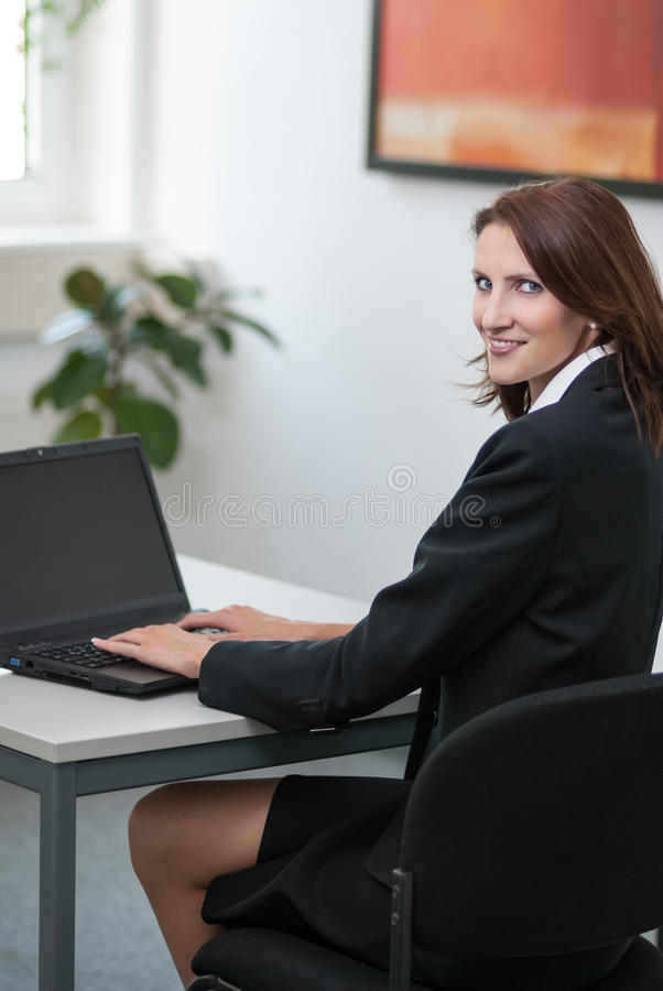 Download Young Attractice Businesswoman Uses Her Laptop Royalty Free Stock Photos - Image: 26990348