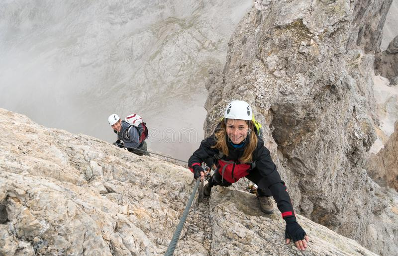 Young climbers on a steep and exposed rock face climbing a Via Ferrata. Young attractiv climbers on a vertical and exposed rock face climbs a Via Ferrata while royalty free stock images