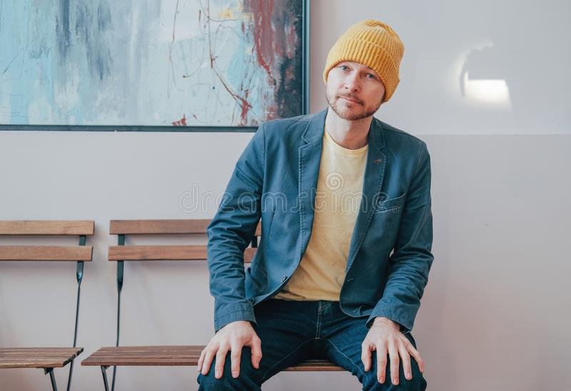 Young attractive adult bearded man hipster in yellow hat sitting on chair and looking at camera, real people lifestyle. The Young attractive adult bearded man stock images