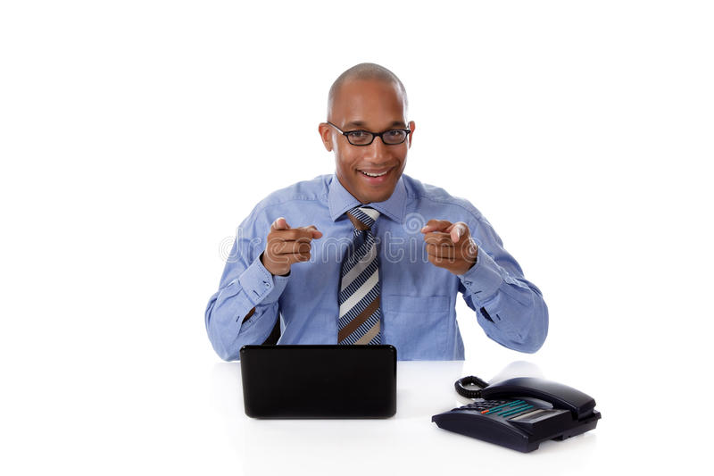 Young attractive African American businessman. In office sitting at desk with a laptop and telephone, pointing . Studio shot. White background stock images