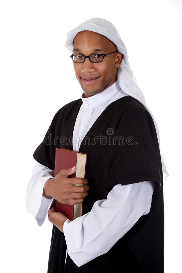 Young attractive African American man, sheikh. Young attractive African American man in sheikh posture dressed in arab garb, holding a book. Studio shot . White stock images