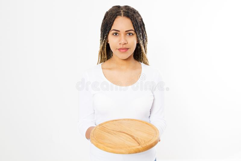 Young attractive african american woman holding empty wood pizza cutting board isolated on white background. Copy space and mock royalty free stock image