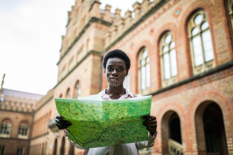 Young attractive afro american female tourist strolling on city streets with map searching right direction to popular showplaces. Young attractive afro american stock images