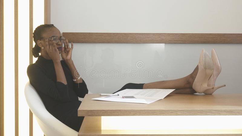 The young attractive afro-american woman with natural make-up is putting her eyeglasses on while sitting with the legs royalty free stock photography