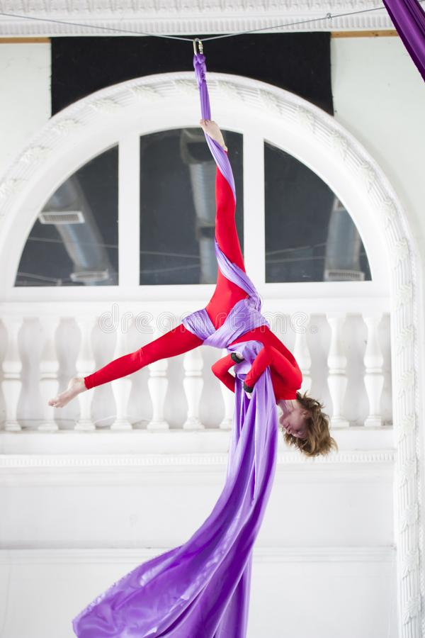 Young attractive air gymnast performs an exercise hanging on aerial silk stock photos