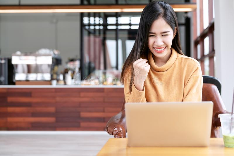 Young attractive asian female student using laptop computer smiling with excited at cafe coffee shop. Happy asian success woman, royalty free stock images